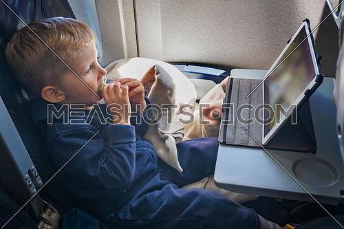 Baby boy is sitting on the plane and eats and looks at the tablet in front of him.