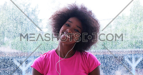 portrait of young afro american woman in gym on workout break while listening music on earphone and dancing rainy day and bad weather outdooor