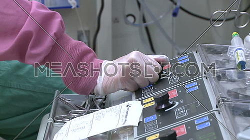 Close shot for surgical technitian hand operates Cardiopulmonary bypass machine