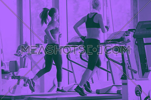 sport, fitness, lifestyle, technology and people concept - smiling woman exercising on treadmill in gym duo tone