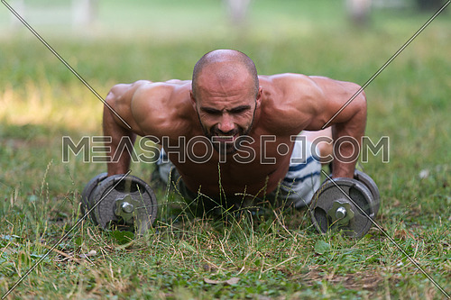 Young Muscular Athlete Doing Push Ups With Dumbbells As Part Of Bodybuilding Training - Outdoors Workout - Sports And Fitness - Concept Of Healthy Lifestyle - Fitness Male