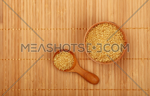 Wooden round scoop spoon and small bowl of brown cane sugar on bamboo mat background, top view