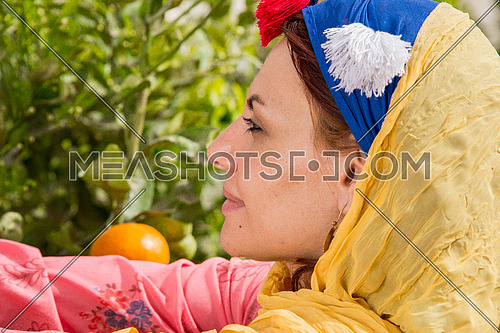 a female farmer in a tangerine feild