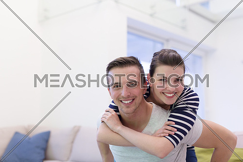 happy young man piggybacking his girlfriend at home