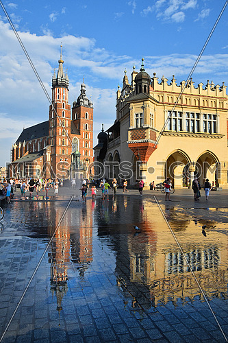 Low angle view of Main Market Square with town hall and Church of Our Lady Assumed into Heaven (Saint Mary Church after rain in Krakow, Poland