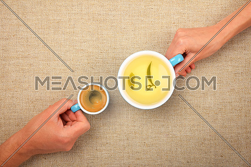 Different habits, two hands, man and woman, holding full cups, small espresso coffee and big green tea with leaves, together over linen canvas background
