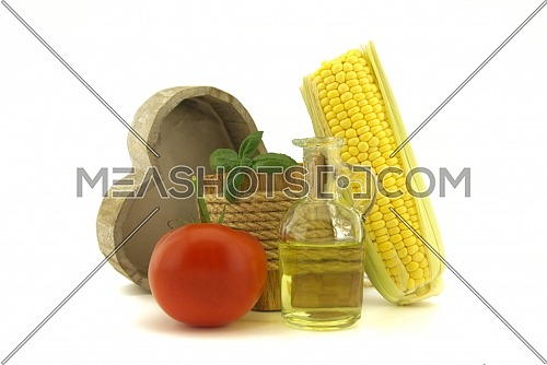 Healthy vegetables including a juicy ripe red tomato and fresh corncob with decanter of olive oil and basil plant in a rustic wooden pot with rope over a white background