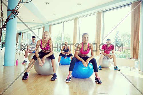 group of people exercise with balls on yoga class in fitness gym