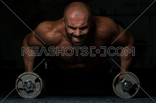 Young Adult Athlete Doing Push Ups With Dumbbells As Part Of Bodybuilding Training In A Dark Room