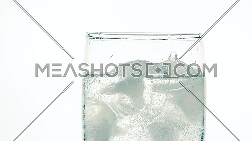 Close up dropping ice cubes in glass of pure clear sparkling water with gas over white background, low angle side view, slow motion