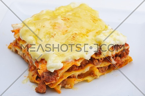 Close-up of a traditional lasagna made with minced beef bolognese sauce topped with basil leafs served on a white plate