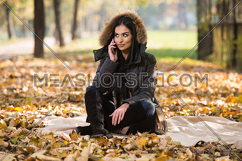 Portrait Of Attractive Young Woman Talking On The Mobile Phone And Sitting On Blanket