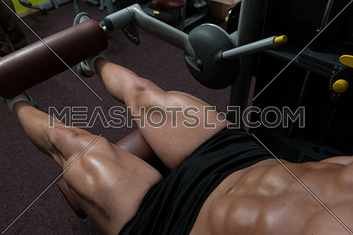 Attractive Young Man Doing Leg Exercises With Machine In Gym