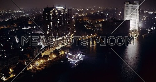 Drone Left of shot from the River Nile revealing The Four Seasons Hotel and Cairo horizon at night
