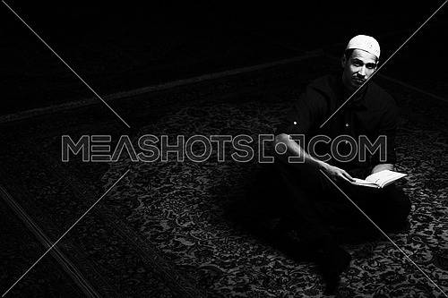 Humble Muslim Man Is Reading The Koran In The Mosque in black and white