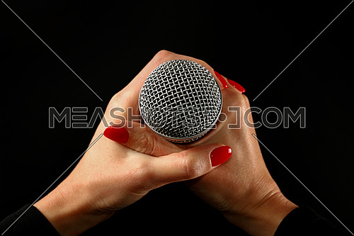 Woman holding microphone with two hands with red nails isolated on black background