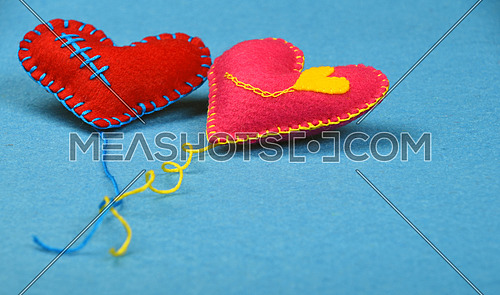 Felt craft and art, two handmade stitched toy hearts with yellow thread, red and pink on blue background, low angle view