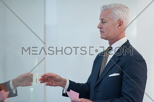 senior business man at modern office making plans and projects with post stickers on glass