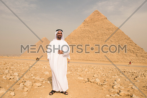 young man as tourist  wearing  arabian traditional clothes in egypt with giza pyramids in background