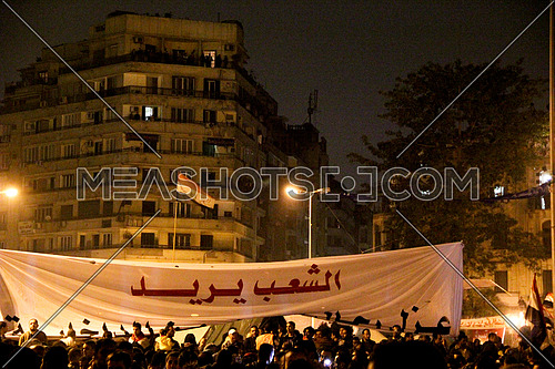 a sign in the middle of tahrir square at night