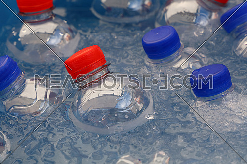 PET plastic bottles of cold still and sparking drinking mineral water with blue and red caps float and chill down in ice and water on retail market display, close up, high angle view