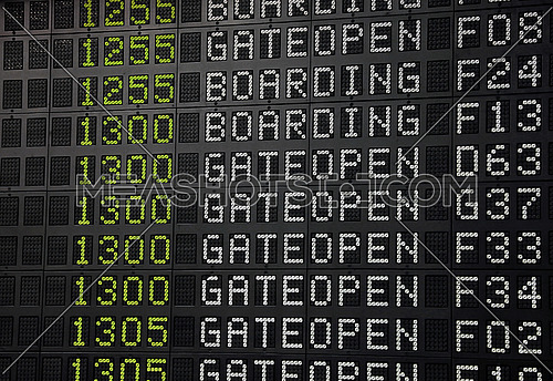 Flight information panel desk at airport, with time, flight number, boarding and gate open messages, close up, low angle view