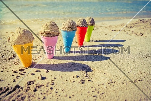 Colorful sand cones in the sand on the beach,summer concept,used split toning for vintage style.