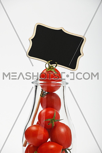 Big glass bottle full of cherry tomatoes and black chalkboard sign over white background as symbol of fresh natural organic juice or ketchup, close up crop