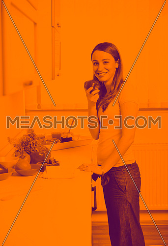 happy young  woman with apple in kitchen and other food and vegetables duo tone