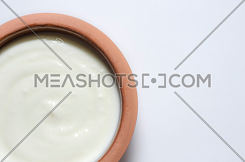 plane white yogurt in pottery plate, close up on a white background