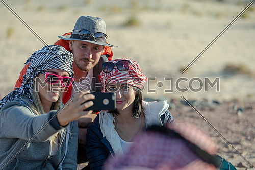 mid shot for group of tourists wearing bedouin traditions headscarf and taking selfies at Ain hodouda in Sinai at day