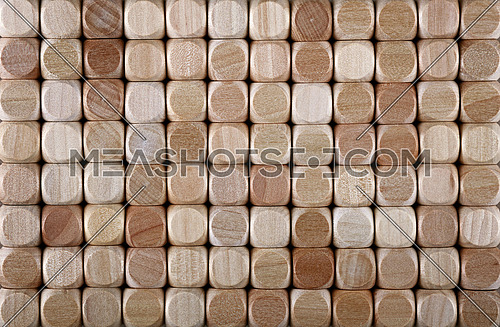 Close up background pattern of natural wooden dice shaped toy building blocks, elevated high angle view, directly above