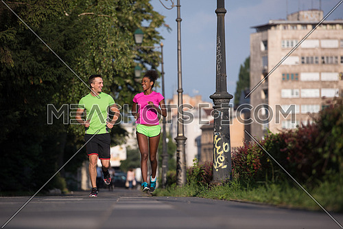 healthy young multiethnic couple jogging in the city on a sunny summer day