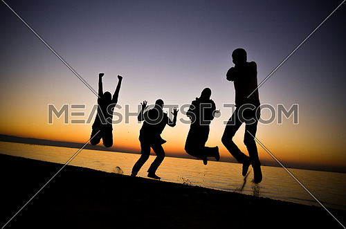 Four friends standing and jumping and having fun at the beach enjoying the golden hour by sunset magic hour