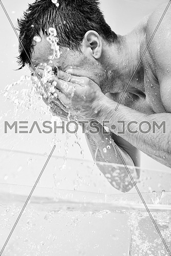 young man washing face with clean water and representing hygiene and mans beauty concept