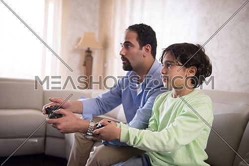 Middle Eastern father and son playing video games and cheerfully spend time on the sofa