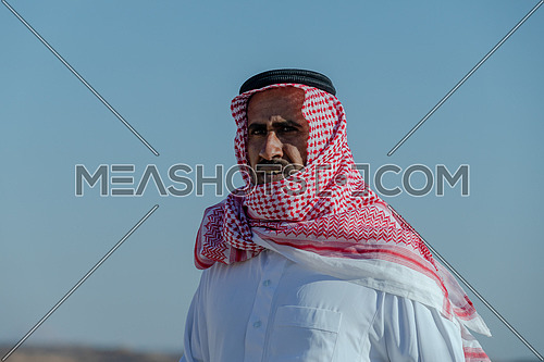 Portrait for bedouin male climbing down rocks at day.