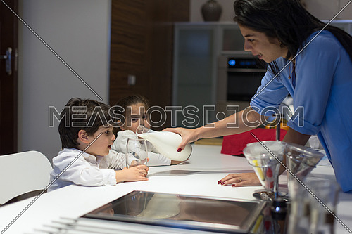 little middle east boy and girl with mom eating snacks and drinking milk in the kitchen with pleasure