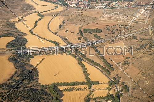 Aerial view of the Madrid region, outside the metropolitan area. Flying over agricultural fields and road. Spain