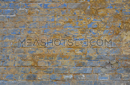 Old grunge vintage yellow painted brick wall with blue paint scale, stains and dirt faded background