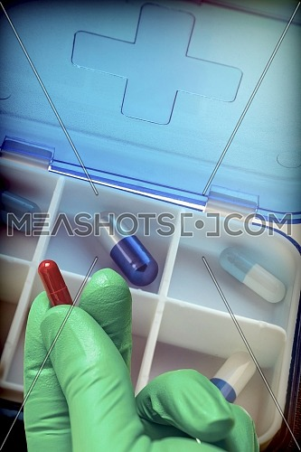 Hand with latex glove supports tablet along with pillbox, conceptual image