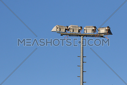 Set of sports lights high on a pole at stadium against blue sky