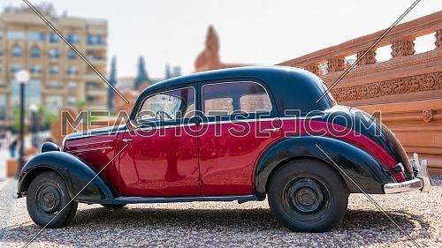 Cairo, Egypt- July 29 2020: 1953 Black and red Mercedes antique car, displayed in front of Baron Empain Palace