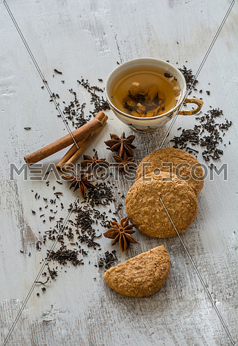 Tea, dried cinnamon, vegan cookies and anise on wooden backgroun