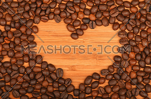 Heart shaped coffee beans frame of Roasted Arabica coffee espresso beans over wooden bamboo board background