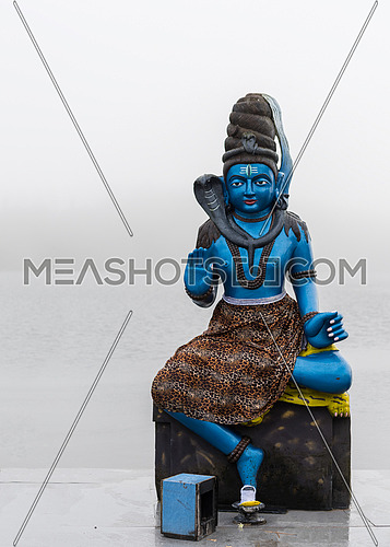 Statue of Shiva in a hindu temple (Grand Basin), in the day with fog ,mystical atmosphere.Mauritius