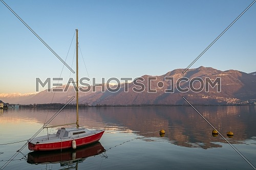 Colorful red boat on stunning mountain lake in Alps during sunset,panorama of Iseo lake from the city of Lovere,Bergamo,Lombardy Italy.