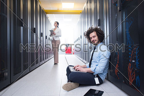 Team of young technicians working together on servers at the data center using laptop and tablet computers