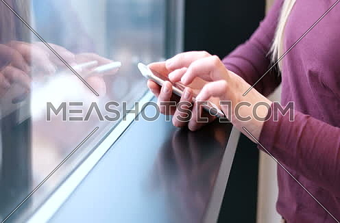 Close up of business woman Hands using cell phone in office interior.
