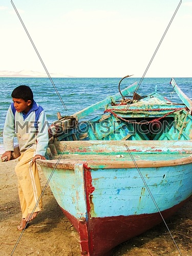Fisher boy sitting on his boat in Fayoum Egypt